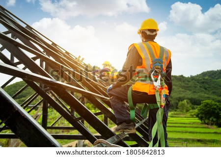 Asian worker wear safety height equipment to install the roof. Fall arrestor device for worker with hooks for safety body harness, Worker as in the construction site