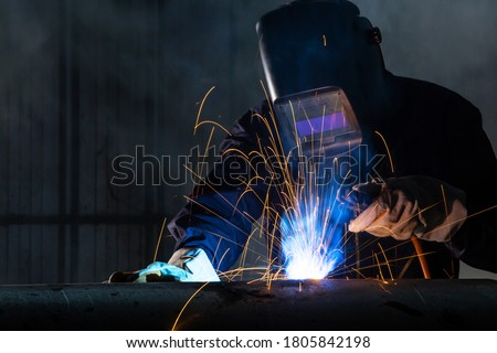 Asian workers wearing safety first uniforms and Welded Iron Mask at Steel welding plants, industrial safety first concept. Photo stock ©