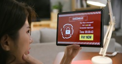 asian worried young woman looking at tablet pc with ransomware attack words on the screen at home
