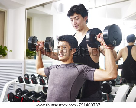 asian young adult man coached by trainer while working out in gym using dumbbells.
