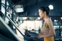 Asian young athlete sportswoman practice workout to maintain muscle in gym or fitness club. Active attractive girl in sport wear exercise by running in Treadmill to burns calories for health in stadiu