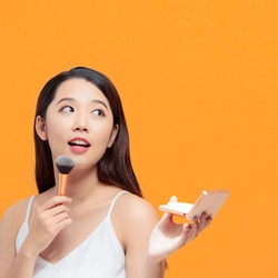 asian young beautiful woman applying cosmetic powder brush on smooth face isolated over yellow background