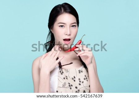 Asian young beautiful woman holding red and green chili pepper, hot and spicy food, natural makeup, beauty face, isolated over blue background.