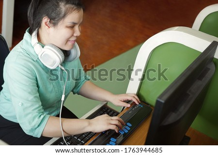 Asian young blind person woman with headphone using computer with refreshable braille display or braille terminal a technology device for persons with visual disabilities.