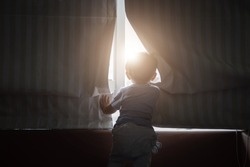 Asian young boy opening the window