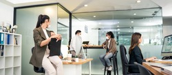 Asian young business people working on computer in office with new normal lifestyle concept. Man and woman wear protective face mask and keep distancing to prevent covid virus after company reopen.