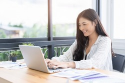Asian young business women work from home new project modern loft,laptop in coffee shop cafe,Analyze plans,papers,  texting keyboard.design notebook quaratine coronavirus,technology startup business