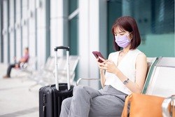 asian young businesswoman wearing face mask and sitting outside is using smart phone with suitcase on her business trip