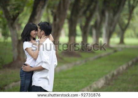 Asian young couple hugging in the park