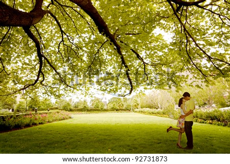 Asian young couple kissing under tree near St. Patrick Cathedral, Melbourne - Australia