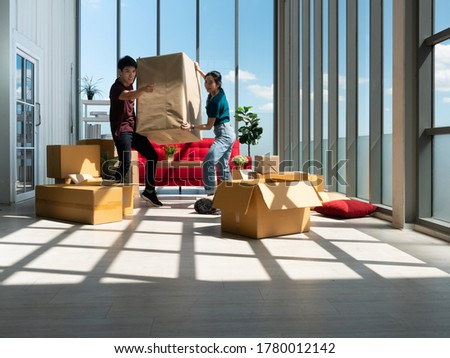 Asian young couple man and woman holding and carrying big cardboard while point out finger the way to moving box position after relocation from apartment to new home within many parcel or carton ストックフォト ©