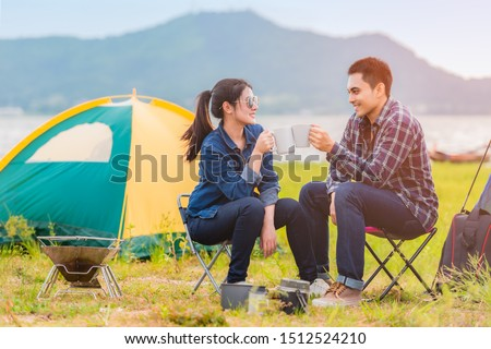Asian young couple sitting drinking coffee to happily near lake and the tent camp on outdoors camping. Lifestyle and camping concept.