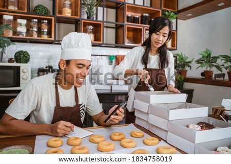 Asian young couple sitting when preparing of donuts order using smartphone to communicate with customers from the kitchen after making donuts together. Foto stock ©
