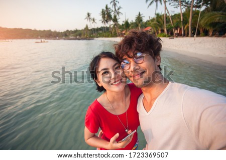 Asian young couple traveller happy in love smiling take a selfie on the beach.
