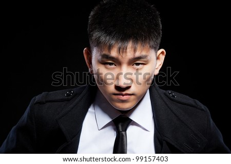 asian young fashion business man confident serious, close up portrait of angry businessman wear elegant jacket coat suit and tie over black background - stock photo