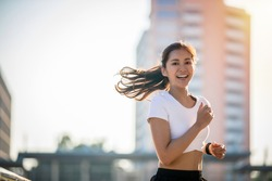 Asian Young fitness sport woman running  and smiling on city road