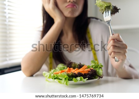 Asian young girl feeling bore to have diet food such as vegetable dish. She holding fork with green salad and wearing measurement tape on neck showing that she must control food for losing her weight. #1475769734