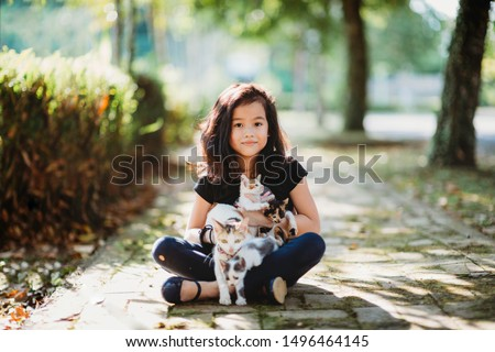 Asian young girl holding a mother cat and kittens in the park under the sun. Pet and domestic animal lover. Happy child in nature during the summer. Cats and family. Friendship and childhood memory.