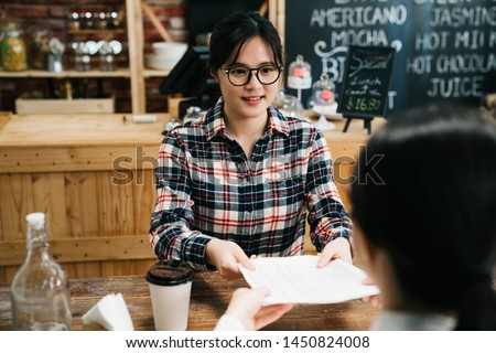 asian young girl in glasses passing over resume to employer in cafe bar interview. polite female applicant smiling to lady hr manager in coffee shop sitting at wooden table start up job meeting.