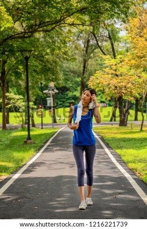Asian young girl relaxing after jogging in park #1216221739