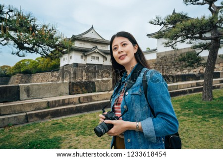 6e4732570d asian young girl tourist holding camera in hands standing in the green park  with osaka castle