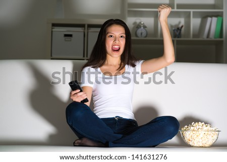 Asian young girl with excitement at night watching TV in the living room