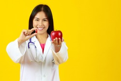 Asian young healthy beautiful female doctor wearing white gown uniform with stethoscope, holding red apple, picking up and showing vitamin capsule pill with isolated yellow background and copy space