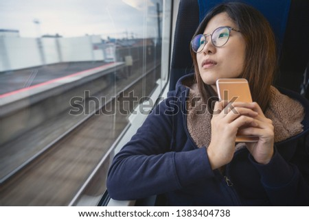 Asian Young lady passenger Sitting in a depressed mood beside the window inside Train which travel between town when travel alone for escape the chaos, traveller and depress concept