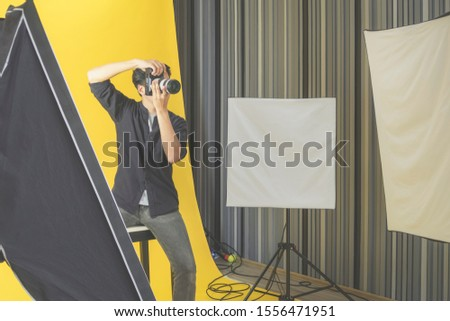 Asian Young male professional photographer shooting photo with a digital camera in a professionally equipped studio.