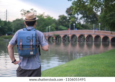 asian young man age 25-30 year tourists backpacker are watching the beauty of the bridge and river in the park and tourist attractions. happily during travel the holidays and relax.