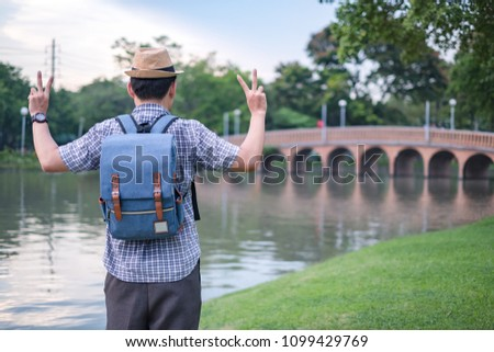 asian young man age 25-30 year tourists backpacker are watching the beauty of the bridge in the park and tourist attractions with two fingers victory sign. happily during travel the holiday and relax