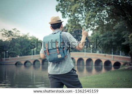 asian young man age 25-30 year tourists backpacker are watching the beauty of the bridge in the park and tourist attractions with thumbs up sign show excellence. happily during travel the holidays