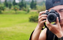 Asian Young man holds a camera in the garden. Using black hat and black tank top.