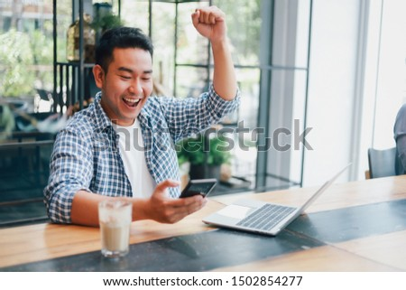 Asian young man in blue shirt working with laptop computer and mobile phone with online job or shopping online happy and smile face in coffee shop cafe