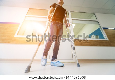 asian Young man on crutches with tree background #1444096508