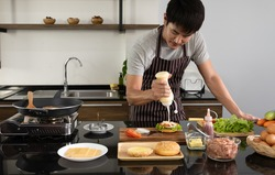 Asian young man prepared the ingredients to cook the hamburger at home, Preparing delicious burger