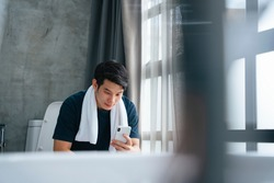 Asian young man relax in toilet and using smartphone.