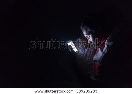 Asian young man using his mobile phone on the bed in dark room. Asian young man sleeping in bed and holding a mobile phone. Concept photo of smart phone addiction