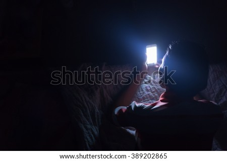 Asian young man using his mobile phone on the bed in dark room.\ Thin guy playing his smartphone on the bed in dark room.