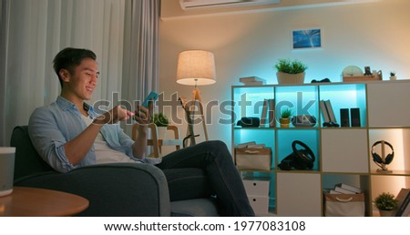 asian young man using smart home app to control light colors in the evening at home Foto stock ©