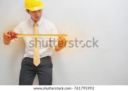 Asian young men, civil engineer holding yellow measurement tape #761795992