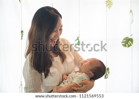 Asian young mother holding her baby in the bosom