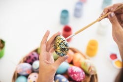 Asian young pretty woman enjoy painting a water colors on fantasy eggs for Easter egg festival. Beautiful colorful fancy Easter egg in bucket. The symbolic of Easter egg festival concept.