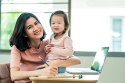 Asian young single mother working on computer, writing note for work from home while taking care little baby girl together due to Covid19 virus pandemic. Woman is busy but happy to stay with family.