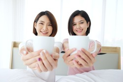 Asian young sisters lovely couple on white bed wake up and smiling with drinking cup of hot coffee together in bedroom. Homosexual women or Lesbian in love. Asian Teenage and Holiday concept.