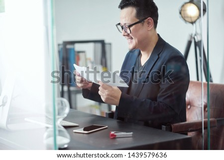 Asian young staff feeling happy while sitting at his working place and get the promotion letter .