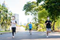 Asian young three woman and man are jogging and exciseing outdoor in city park and wearing protective mask on face for stay in fit during Covid-19 pandemic in Bangkok, Thailand.