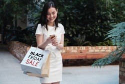 Asian young woman carrying shopping bags and shopping online, Black friday sale concept