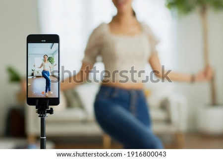 Asian young woman created her dancing video by smartphone camera. To share video to social media application.