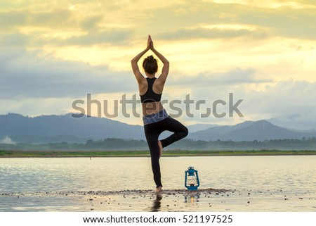Asian Young woman doing yoga in morning park,Woman Yoga relax in nature,Asian woman is practicing yoga at mountain lake,silhouette yoga,yoga relax
